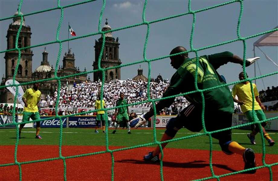 The goal keeper for team South Africa blocks a shot by team Mexico during the Homeless World Cup soccer tournament in Mexico City's Zocalo plaza, Saturday, Oct. 6, 2012. The Homeless World Cup organization puts together the yearly championship in cities worldwide since 2003, using soccer as a means to help homeless people change their lives. (AP Photo/Marco Ugarte) Photo: Marco Ugarte, AP / AP
