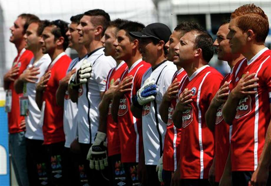 Chile's team sings their national anthem before playing a soccer game against team Italy at the 10th annual Homeless World Cup soccer tournament in Mexico City's Zocalo plaza, Saturday, Oct. 6, 2012.  The Homeless World Cup organization puts together the yearly championship in cities worldwide since 2003, using soccer as a means to help homeless people change their lives. (AP Photo/Marco Ugarte) Photo: Marco Ugarte, AP / AP