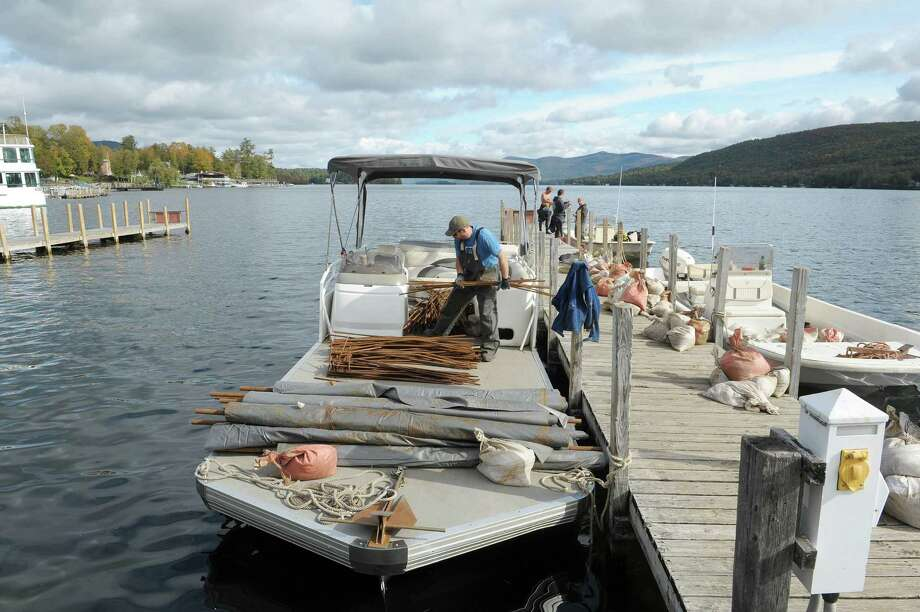 Kyle Jaquis, left, a diver with Aquatic Invasive Management loads some rebar onto a boat on Monday, Oct. 8, 2012 in Lake George, NY.  Crews with the company are working on laying down mats to cover over areas of  Asian clams and using rebar and sandbags to keep the mats sealed around the area.  The mats keep the clams from feeding and getting oxygen which kills them.   (Paul Buckowski / Times Union) Photo: Paul Buckowski