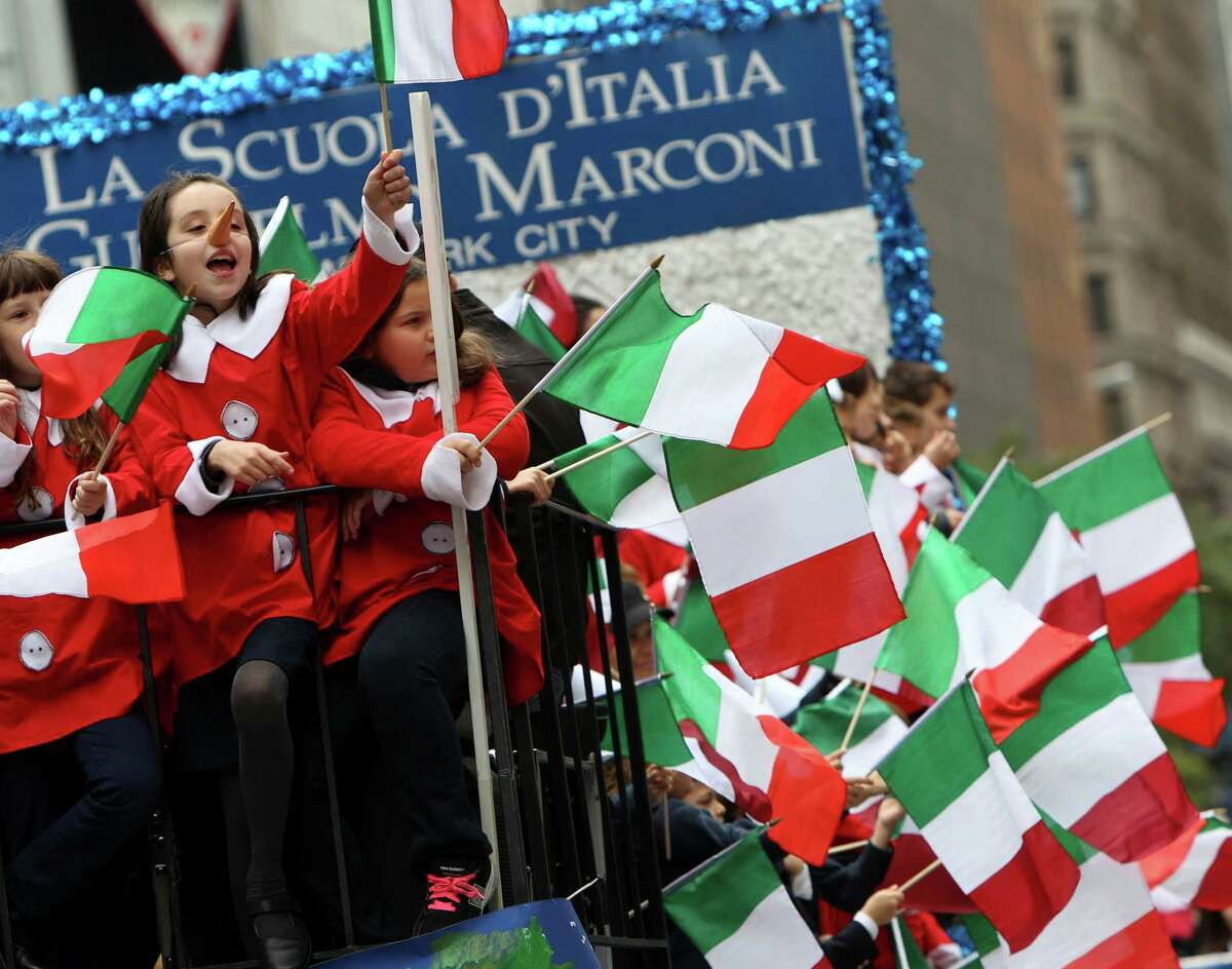 School children wave Italian flags as they pass by on a float during the Columbus Day parade in New York, Monday, Oct. 8, 2012.