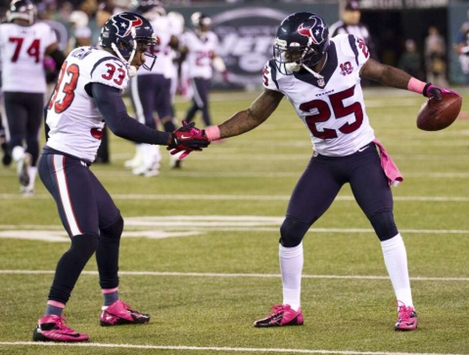 Texans defensive backs Troy Nolan (33) and Kareem Jackson (25) celebrate Jackson's interception of a pass by New York Jets quarterback Mark Sanchez late in the game. (Houston Chronicle)
