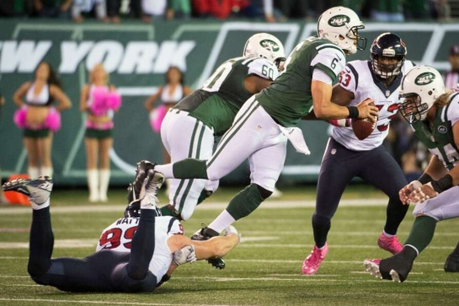 Jets quarterback Mark Sanchez (6) is tripped up by Texans defensive end J.J. Watt (99) during the fo