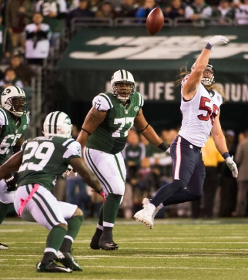 Texans linebacker Brooks Reed (58) reaches for a tipped pass intended for Jets running back Bilal Powell (29) during the second quarter. (Houston Chronicle)