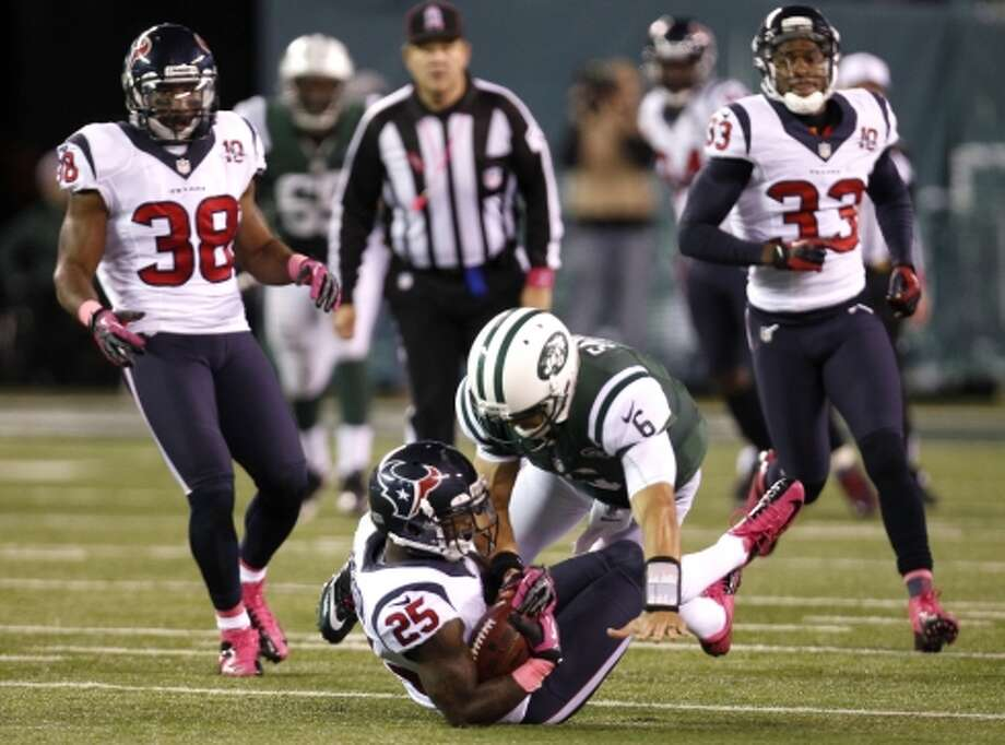 Texans cornerback Kareem Jackson (25) is stopped by Jets quarterback Mark Sanchez (6) after intercepting a Sanchez pass during the second half. (Houston Chronicle)