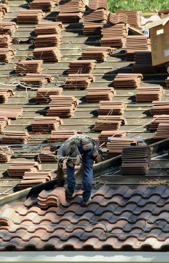 A workers put shingles on a new home under construction at the Commons of Lake Houston, a 4,200 acre development east of Kingwood on Lake Houston. Photo: David Hopper / freelance