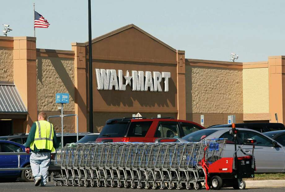 FILE - In this March 17, 2010 file photo, a worker gathers shopping carts near a Wal-Mart store in Washington Township, N.J. The Supreme Court has ruled for Wal-Mart in its fight to block a massive sex discrimination lawsuit on behalf of women who work there. (AP Photo/Mel Evans, File) Photo: Mel Evans / AP