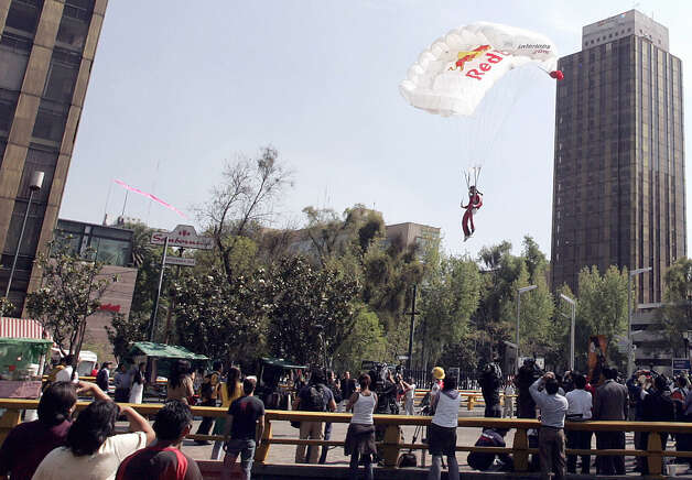 "Felix Baumgartner lands after jumping from the top floor of Mexico City's ""Torre Mayor"" skyscrapper, 