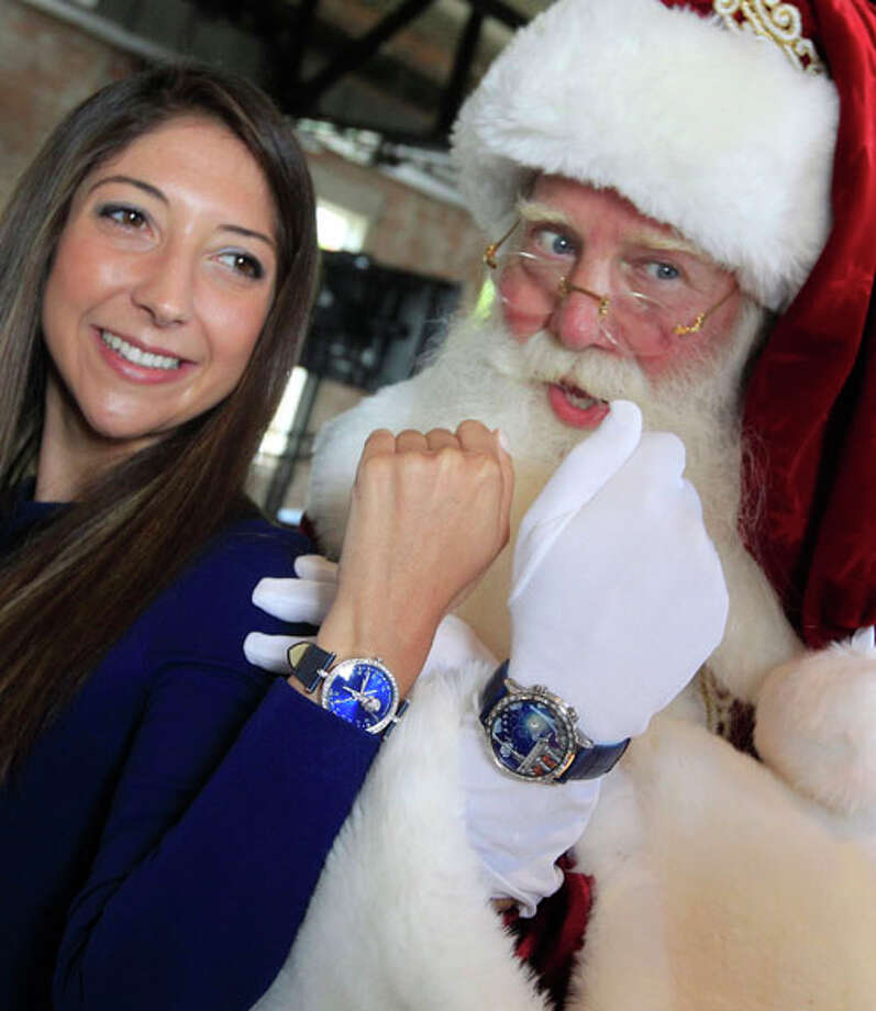 "Brady White portrays Santa Claus, right, as he and model Marisa Neira show off his and hers ""Poetic Wish"" watches from Van Cleef & Arpels during the unveiling of the Neiman Marcus 2012 Christmas Book in Dallas, Tuesday, Oct. 9, 2012.  The Van Cleef & Arpels watches include a trip to Paris and Geneva that is priced for sale at $1,090,000. Photo: LM Otero, . / AP"