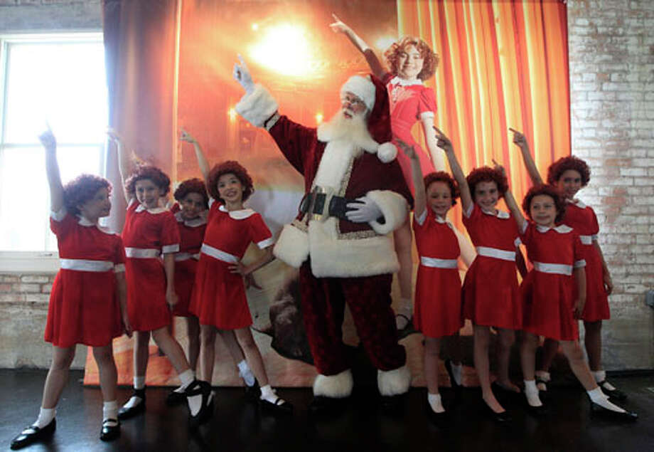 With several Annies on hand, Brady White portrays Santa Claus, center, as he and the little actresses display the a gift Annie:The Musical Walk-on Role during the unveiling of the Neiman Marcus 2012 Christmas Book in Dallas, Tuesday, Oct. 9, 2012. For $30,000, the gift buys a walk on role in the Broadway musical. Photo: LM Otero, . / AP