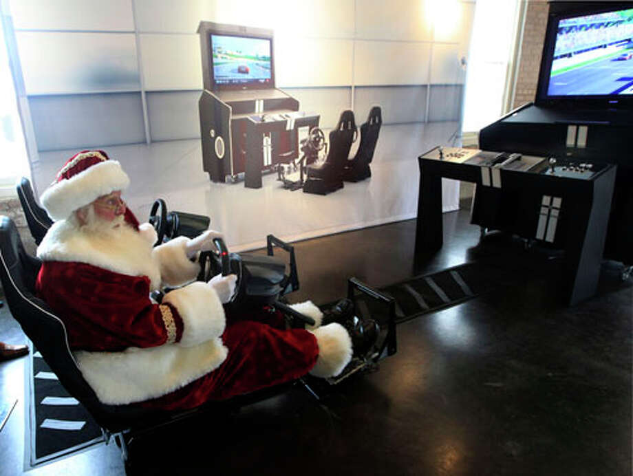 Santa Claus, portrayed by Brady White, plays on the custom made Pinel & Pinel Arcade PS Trunk system during the unveiling of the Neiman Marcus 2012 Christmas Book in Dallas, Tuesday, Oct. 9, 2012. The fantasy gift arcade is priced for sale at $90,000. Photo: LM Otero, . / AP