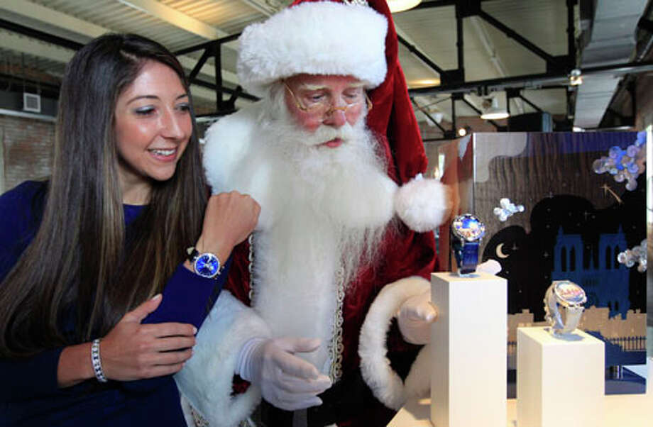 "Brady White portrays Santa Clause, right, as he and model Marisa Neira show off his and hers ""Poetic Wish"" watches from Van Cleef & Arpels during the unveiling of the Neiman Marcus 2012 Christmas Book in Dallas, Tuesday, Oct. 9, 2012.  The Van Cleef & Arpels watches include a trip to Paris and Geneva that is priced for sale at $1,090,000. Photo: LM Otero, . / AP"