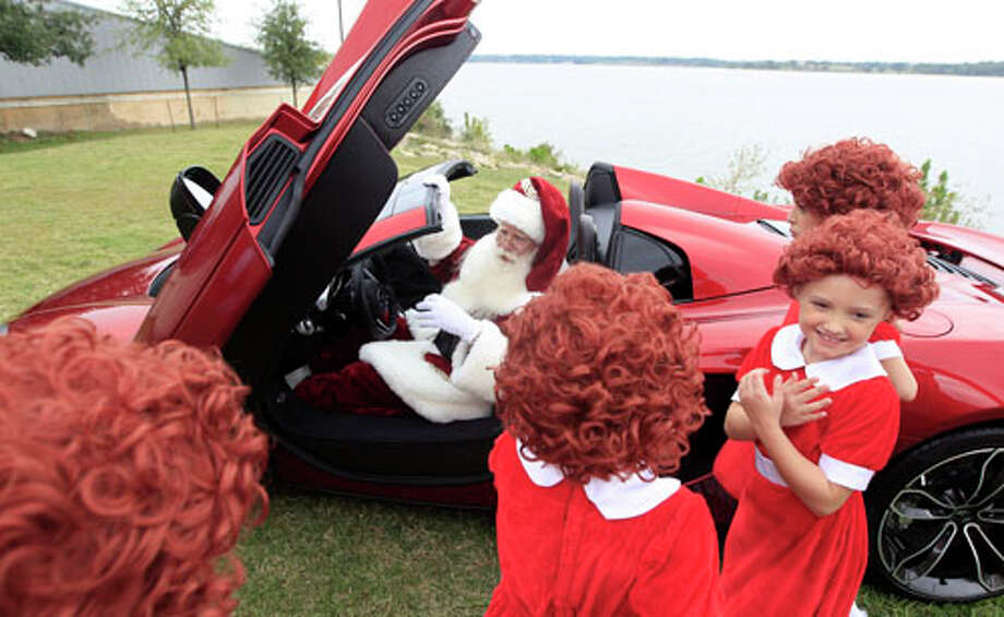 With several Annies on hand, Brady White portrays Santa Claus as he displays a 2013 McLaren 12C spider sports car during the unveiling of the Neiman Marcus 2012 Christmas Book in Dallas, Tuesday, Oct. 9, 2012. Photo: LM Otero, . / AP