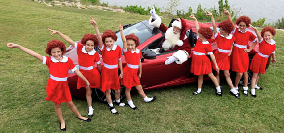 With several Annies on hand, Brady White portrays Santa Claus, center, as they pose with a 2013 McLaren 12C spider sports car during the unveiling of the Neiman Marcus 2012 Christmas Book in Dallas, Tuesday, Oct. 9, 2012. Shoppers can shell out $30,000 buying a walk on role in the Broadway musical Annie and $354,000 gets the car. Photo: LM Otero, . / AP