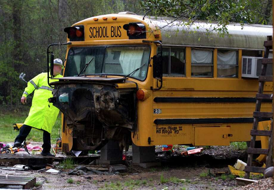 A Montgomery Count sheriff's deputy knocks on the door to an old school bus in Splendora where two children were found living on their own in March. (this photo doesn't have a photographer's credit on the file.) Photo: Houston Chronicle File