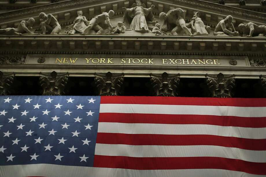 An American flag hangs over the New York Stock Exchange on October 9, 2012 in New York City. (Getty Images) Photo: Spencer Platt, Getty Images / 2012 Getty Images