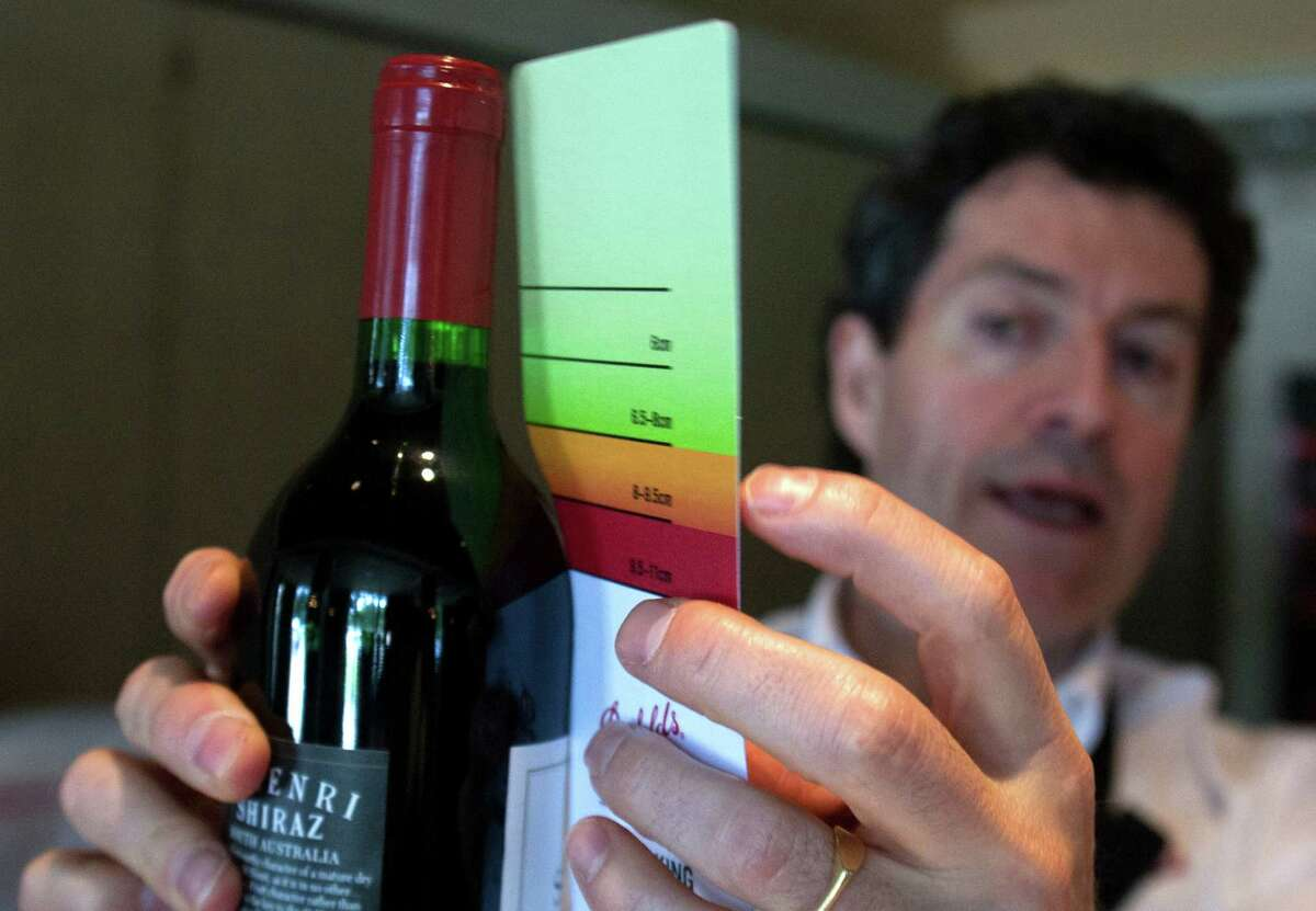 Australian winery Penfolds' head winemaker Peter Gago examines a wine bottle using a color-coded card that fits against the neck of a bottle to determine if recorking is an option.