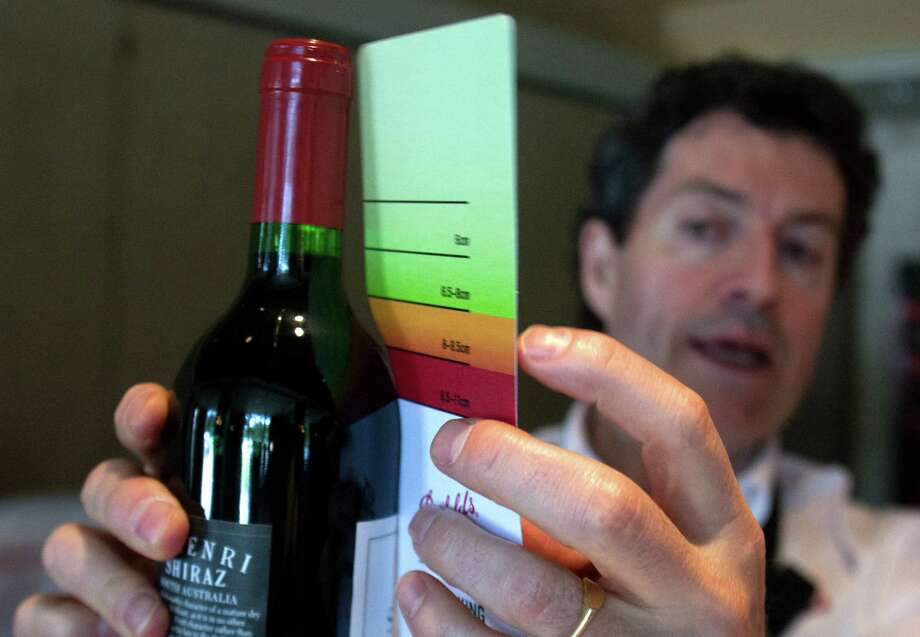 Australian winery Penfolds' head winemaker Peter Gago examines a wine bottle using a color-coded card that fits against the neck of a bottle to determine if recorking is an option. Photo: J. Patric Schneider / © 2012 Houston Chronicle