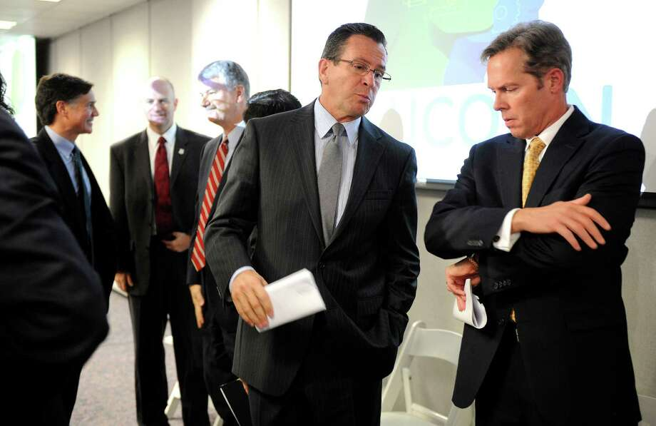 Connecticut Gov. Dannel P. Malloy, center, talks with Bob Gilligan, chief executive officer of General Electric's Industrial Solutions business, after a news conference announcing a $7.5 million partnership between GE and the University of Connecticut in the technology sector to spark innovation in electrical distribution products, Tuesday, Oct. 9, 2012, at the company's Plainville Conn. offices.  (AP Photo/The Bristol Press, Mike Orazzi) MANDATORY CREDIT, MAGS OUT, NO SALES Photo: Mike Orazzi, Associated Press / Associated Press