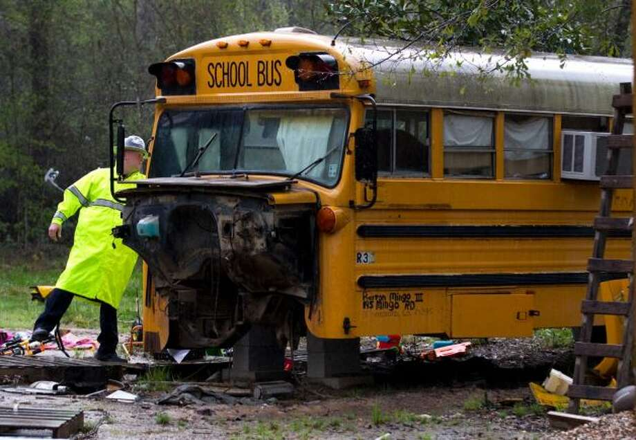 A Montgomery Count sheriff's deputy knocks on the door to an old school bus in Splendora where two children were found living on their own in March.. Photo: Houston Chronicle File / HC