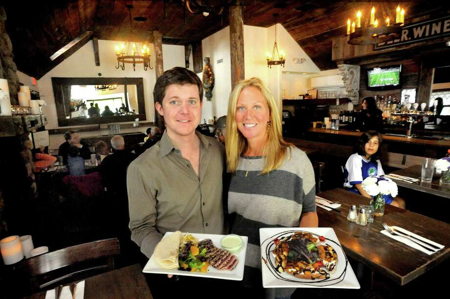 Devin O'Keeffe stands with Daneen Grabe, who is the owner of Little Pub in Ridgefield, holding two signature dishes on Saturday, Sept. 22, 2012. Ahi Tuna Tacos are shown at left and Harvest Bruschetta is at right. Photo: Michael Duffy / The News-Times