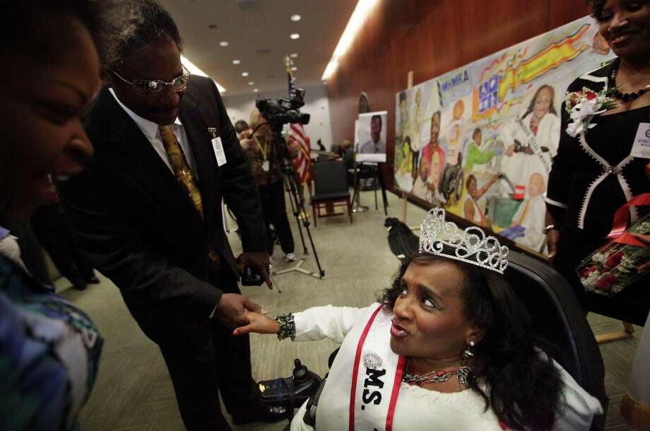 """You got me!"" says Ms. Wheelchair of Texas Tina X. Williams, 45, while shaking hands with Artist Doyle Burley after the unveiling of the mural ""Out of the Shades"" at City Hall Annex on Tuesday, Oct. 9, 2012, in Houston.  Williams is among the people depicted in the mural, which shows the many faces of people with disabilities. The mural was unveiled in October, which is Persons with Disabilities History and Awareness Month in Texas.  Photo: Mayra Beltran, Houston Chronicle / © 2012 Houston Chronicle"