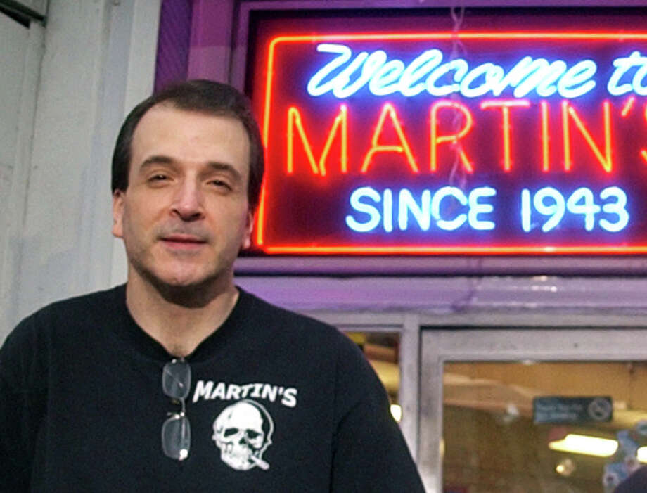 Kris Kuchta stands in front of Martin's Smoke Shop and Convenience Store in Stratford, Conn. on Wednesday December 21, 2011. Kuchta, who has worked at MartinâÄôs News for 29 years, was arrested Tuesday and charged with stealing more than $100,000 from the store over a 10-year period. Photo: Christian Abraham / Connecticut Post