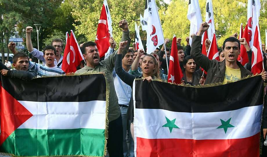 Young Turkish adults conduct an antiwar protest in Ankara with Turkish, Syrian and Palestinian flags. Photo: Adem Altan, AFP/Getty Images