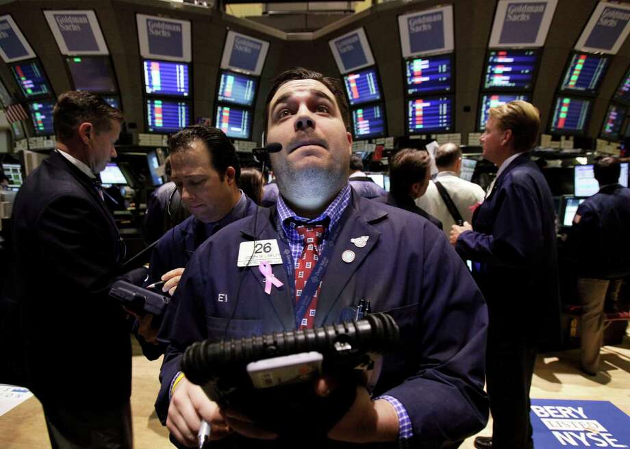 Trader Joseph Lawler, center, works on the floor of the New York Stock Exchange Tuesday, Oct. 9, 2012. Another dire prediction about global economic growth is sending stocks lower on Wall Street in early trading on Tuesday. (AP Photo/Richard Drew) Photo: Richard Drew / AP