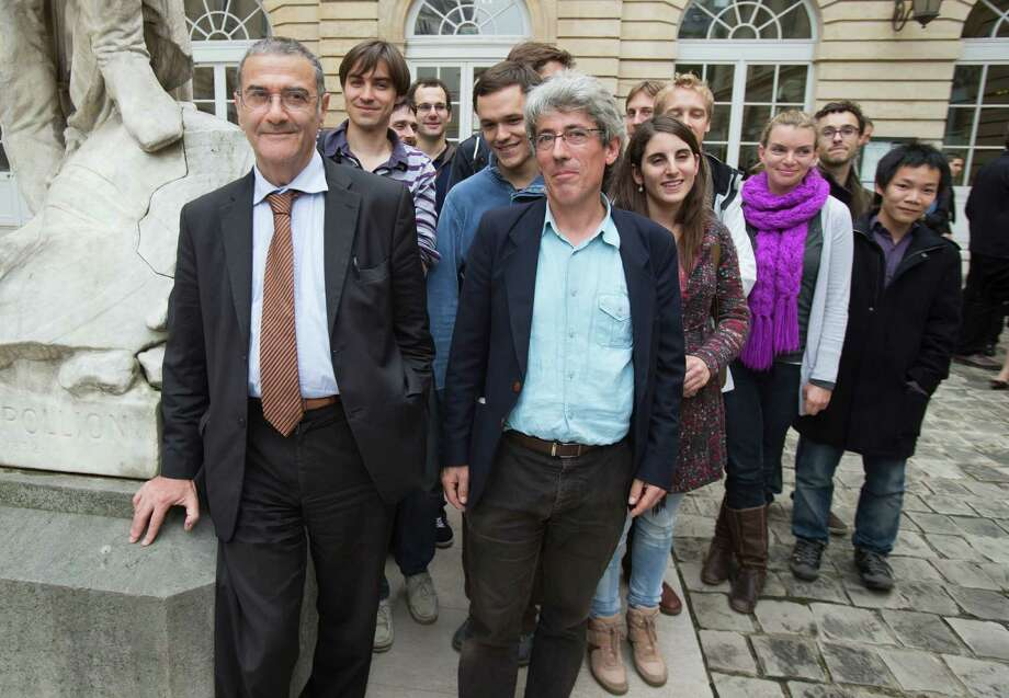 Serge Haroche of France, left, winner of the 2012 Nobel Prize in physics, poses with his research team at the College de France in Paris, Tuesday, Oct. 9, 2012. Haroche and American David Wineland shared the 2012 Nobel Prize in physics Tuesday for inventing methods to observe the bizarre properties of the quantum world, research that has led to the construction of extremely precise clocks and helped scientists take the first steps toward building superfast computers.  Photo: Michel Euler / AP