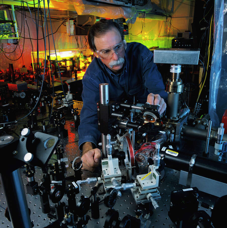 "In this 2003 photo, physicist David Wineland adjusts an ultraviolet laser beam used to manipulate ions in a high-vacuum apparatus containing an ""ion trap"" used to demonstrate the basic operations required for a quantum computer. Wineland and Serge Haroche of France shared the 2012 Nobel Prize in physics Tuesday, Oct. 9, 2012 for inventing methods to observe the bizarre properties of the quantum world, research that has led to the construction of extremely precise clocks and helped scientists take the first steps toward building superfast computers.  Photo: Geoffrey Wheeler / NIST"