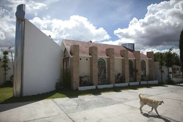 A dog walks near a tomb that was allegedly built by Heriberto Lazcano Lazcano, alleged leader of the Zetas, at a cemetery in the neighborhood of Tezontle in Pachuca, Mexico, Tuesday, Oct. 9, 2012. The tomb is a copy of an actual church in Tezontle, which at one point had a plaque naming Lazcano as the donor. Mexico's Navy says fingerprints confirm that cartel leader Lazcano, an army special forces deserter, was killed Sunday, Oct. 7, 2012 in a firefight with marines in the northern state of Coahuila on the border with the Texas. (AP Photo/Alexandre Meneghini) Photo: Alexandre Meneghini, Associated Press