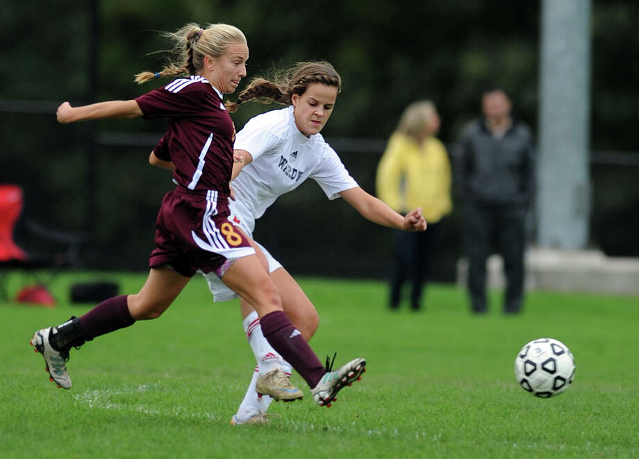 St. Joseph's Samantha Grasso, left, and Fairfield Warde's Virginie Larouche chase down the ball during their soccer match Tuesday, Oct. 9, 2012 at Fairfield Warde High School. Photo: Autumn Driscoll / Connecticut Post