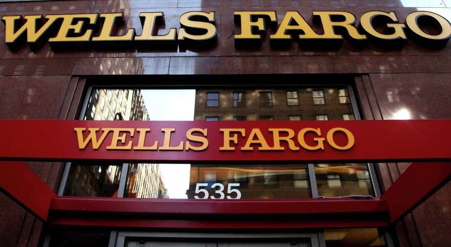 FILE-In this May 6, 2012, file photo, a Wells Fargo sign is displayed at a branch in New York.  The federal government sued Wells Fargo Bank in New York on Tuesday, Oct. 9, 2012, blaming the nation's largest originator of home mortgages for thousands of loan defaults over the last decade(AP Photo/CX Matiash, File) Photo: CX Matiash / AP
