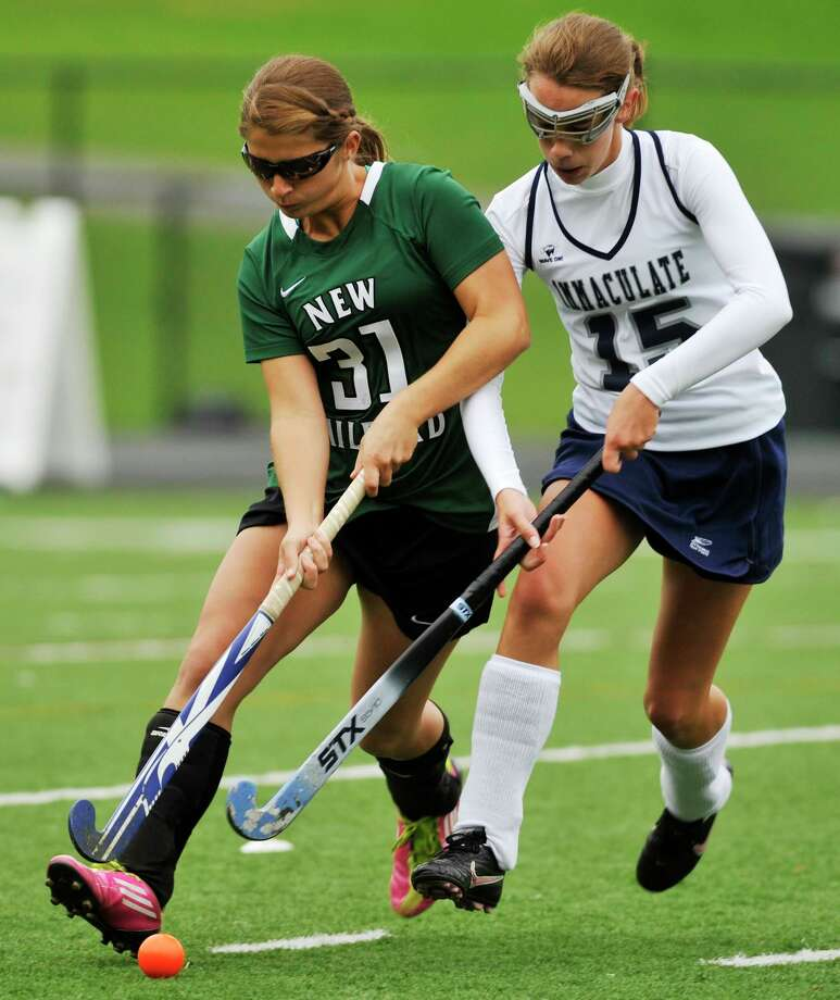 New Milford's Meghan Lacey fends off Immaculate's Katherine Archer during their game at Immaculate High School in Danbury on Tuesday, Oct. 9, 2012. New Milford won, 4-0. Photo: Jason Rearick / The News-Times