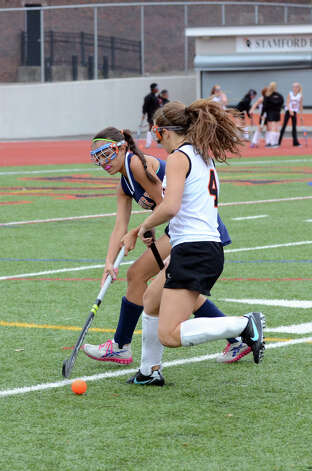 Danbury's Jen Bichof (2) defends against Stamford's Sarah Abruzzini (4) during the field hockey game at Stamford High School on Tuesday, Oct. 9, 2012. Photo: Amy Mortensen / Connecticut Post Freelance