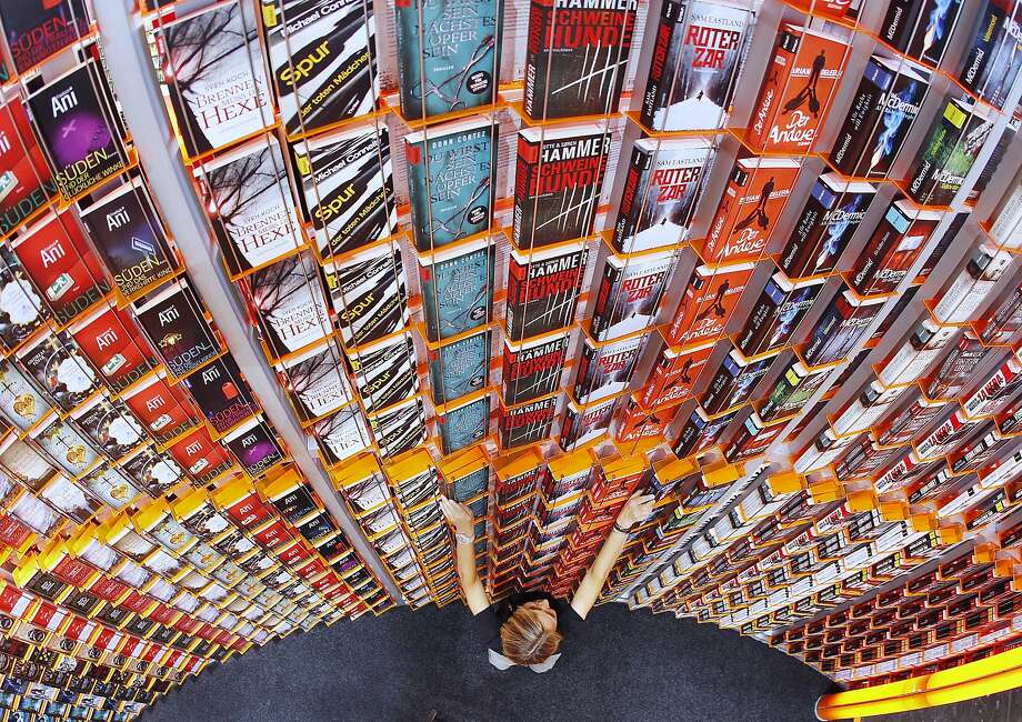 A women arranges books on a shelf at the Frankfurt Book Fair that will be opened later in the day  in Frankfurt, Germany, Tuesday, Oct. 9, 2012. New Zealand is this year's  guest of honor at the book fair. (AP Photo/Michael Probst) Photo: Michael Probst, Associated Press