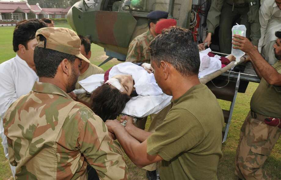 Pakistani soldiers carry wounded Malala Yousufzai on Wednesday from a helicopter to a military hospital in Peshawar, Pakistan. A Taliban gunman shot and wounded the 14-year-old activist. / Inter Services Public Relations