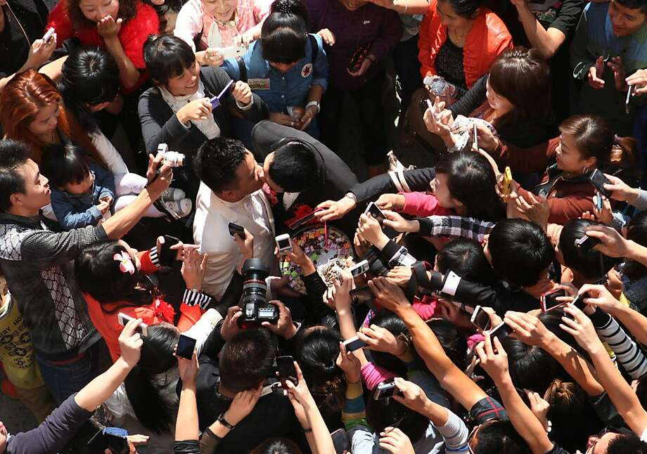 A crowd watches gay couple Liu Wangqiang and Lu Zhong kiss in 2012 after they wed in Tuorong, China. Photo: Str, AFP/Getty Images