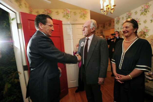 At left, Connecticut Gov. Dannel P. Malloy shakes hands with Democrat John Blankley at Blankley's Greenwich home, Tuesday night, Oct. 9, 2012. Standing behind Blankley is his wife, Vera.  Blankley is running against Republican incumbent state Rep. Livvy Floren, for the 149th District seat. Photo: Bob Luckey / Greenwich Time