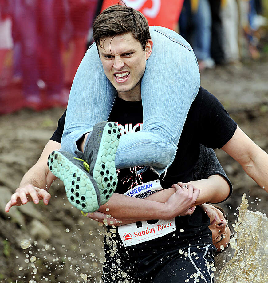 Anne Murray tries to keep her face out of the muddy waters as she is carried by her husband, Sean Murray, during the 2012 North American Wife Carrying Championship Saturday, Oct. 6, 2012 in Newry, Maine. The duo placed tenth with a time of 1:07.46. Photo: Amber Waterman, Associated Press / Sun Journal