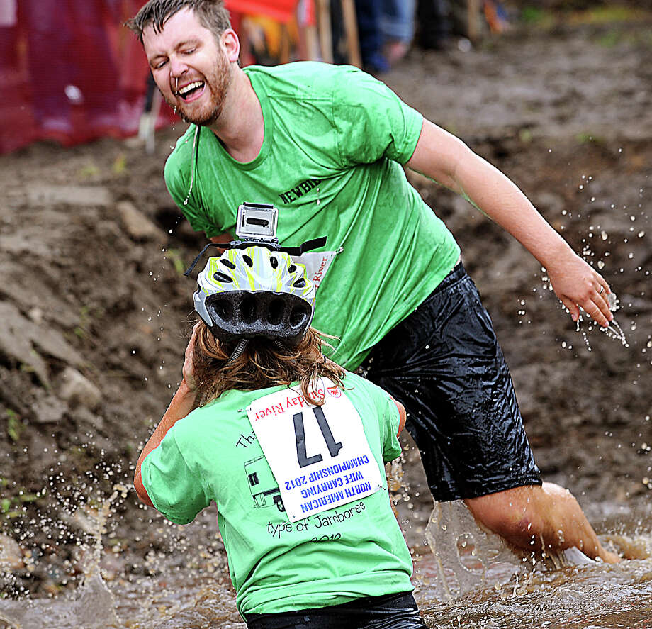 Arthur and Jenna Aery come up laughing despite taking a fall in the water hazard during at the 2012 North American Wife Carrying championship Saturday, Oct. 6, 2012 at Sunday River in Newry, Me. Photo: Amber Waterman, Associated Press / Sun Journal
