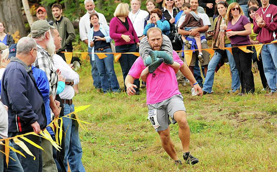 Jesse Wall rounds the bend carrying Christine Arsenault, from South Paris, during the 2012 North American Wife Carrying Championship Saturday, Oct. 6, 2012 in Newry, Me. The duo took second place with a time of 53.22. Photo: Amber Waterman, Associated Press / Sun Journal