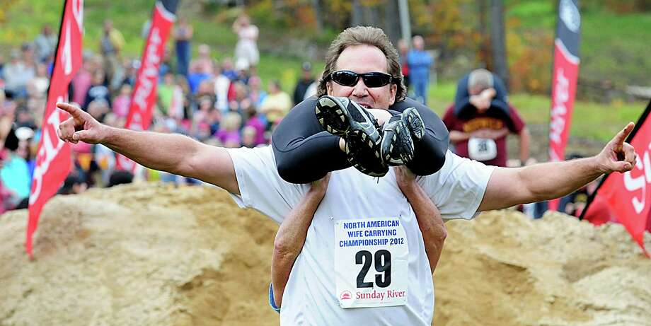 Robert Robbins, carrying Jill Robbins, celebrates his finish at the 2012 North American Wife Carrying championship Saturday, Oct. 6, 2012 at Sunday River in Newry, Me. Photo: Amber Waterman, Associated Press / Sun Journal