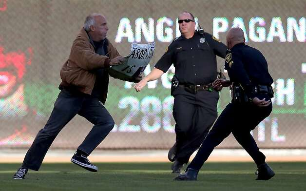 CINCINNATI, OH - OCTOBER 09:  Police chase a man who runs onto the field holding a sign saying 'Abortion is Sin' before the Cincinnati Reds take on the San Francisco Giants in Game Three of the National League Division Series at the Great American Ball Park on October 9, 2012 in Cincinnati, Ohio.  (Photo by Jonathan Daniel/Getty Images) Photo: Jonathan Daniel, Getty Images