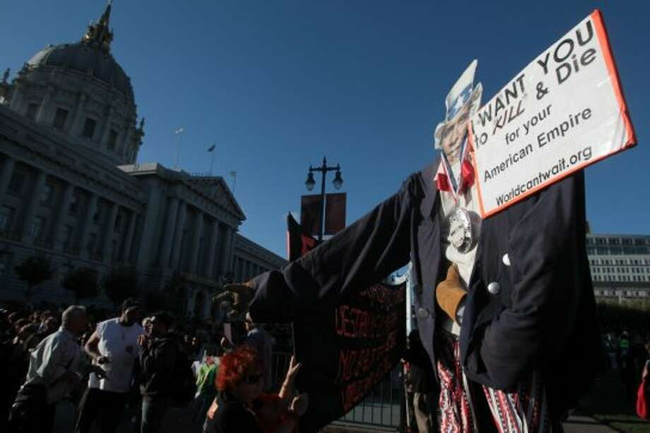 War protesters stand with an effigy of President Barack Obama as supporters of the President wait in line to attend a campaign event in San Francisco on Monday, Oct. 8, 2012. (AP Photo/Mathew Sumner) (Associated Press)