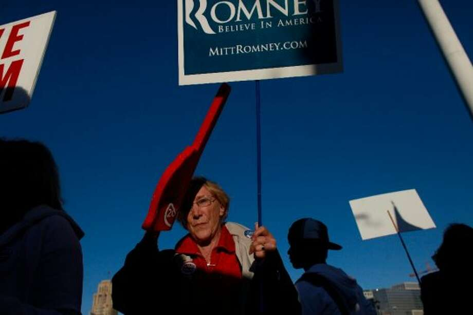 Romney supporter, Fran Cavenaugh, of Walnut Creeks, tries to send a message to Obama supporters at they wait for the president to arrive for a fundraiser at the Bill Graham Civic Auditorium on Monday Oct. 10, 2012 in San Francisco, Calif. (The Chronicle)
