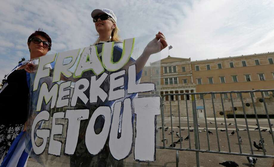Demonstrator holds an anti-Merkel banner  prior to a protest in front of the Greek Parliament in Athens on Tuesday Oct. 9, 2012. German Chancellor Angela Merkel makes her first visit to Greece since the eurozone crisis began three years ago. Her five-hour stop is seen by the government as a historic boost for the country's future in Europe's shared currency, but by protesters as a harbinger of more austerity and hardship. More than 7,000 police will be on hand, cordoning off parks and other sections of central Athens, to keep demonstrators away from the German leader who is due to arrive Tuesday in the Greek capital for talks with conservative Prime Minister Antonis Samaras. (AP Photo/Lefteris Pitarakis) Photo: Lefteris Pitarakis