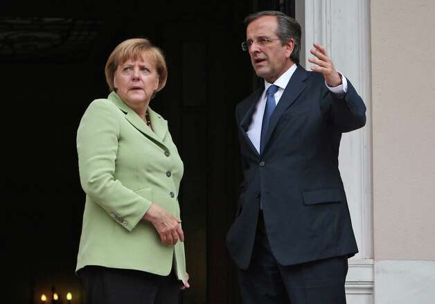 Greece's Prime Minister Antonis Samaras, right, and Germany's Chancellor Angela Merkel speak before their meeting at the Maximos mansion in Athens, Tuesday, Oct. 9, 2012. Amid draconian security measures and a mass protest, German Chancellor Angela Merkel arrived Tuesday for her first visit to Greece since the eurozone crisis began there three years ago. Her five-hour stop is seen by the Greek government as a historic boost for the country's future in Europe, but by protesters as a harbinger of more austerity and hardship.   (AP Photo/Thanassis Stavrakis, Pool) Photo: Thanassis Stavrakis