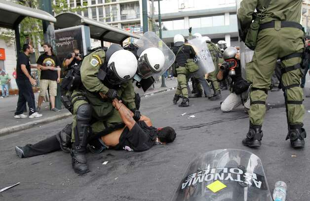 Riot police arrest a demonstrator during clashes in front of the parliament in Athens, Tuesday, Oct. 9, 2012. German Chancellor Angela Merkel got a hostile reception from ordinary Greeks Tuesday when she flew into Athens on her first visit to the country since its debt crisis erupted three years ago. (AP Photo/Nikolas Giakoumidis) Photo: Nikolas Giakoumidis