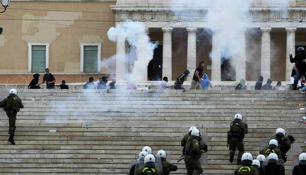 Protesters are chased by riot police during clashes in front of the parliament in Athens, Tuesday Oct. 9, 2012. German Chancellor Angela Merkel got a hostile reception from ordinary Greeks Tuesday when she flew into Athens on her first visit to the country since its debt crisis erupted three years ago. (AP Photo/Nikolas Giakoumidis) Photo: Nikolas Giakoumidis